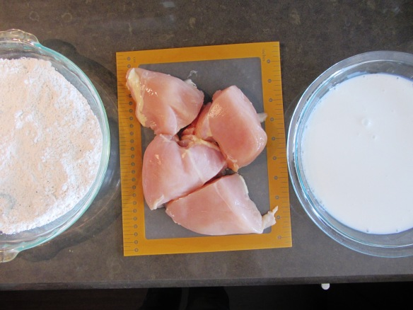 Get your chicken station ready: Seasoned flour, halved chicken breasts, and buttermilk ready to go.