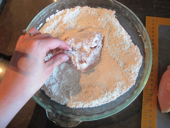 Take one chicken breast half and dredge in the flour.