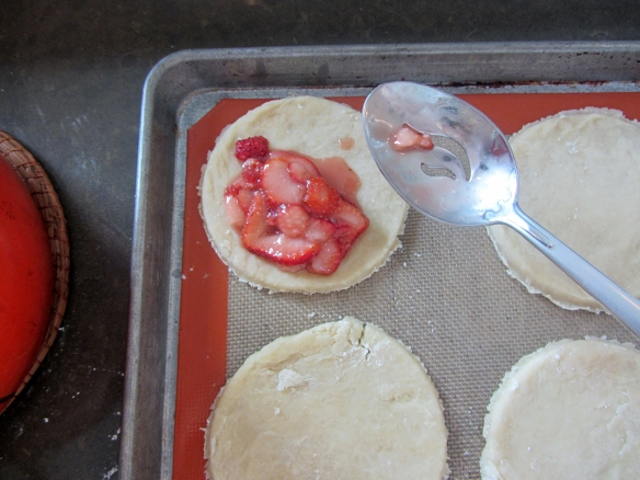 Spoon the strawberries onto half of each piece of dough.  I used a slotted spoon in hopes that my strawberry juice would not get out of hand.