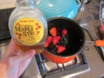 Add berries and maple syrup to a saucepan.