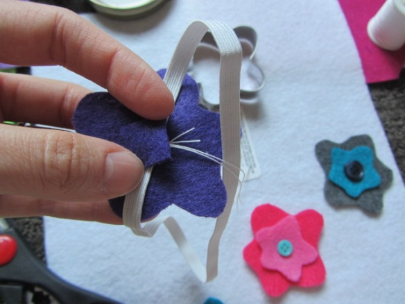 Sew the felt pieces with the button onto the elastic band.  Then cut out a small piece of felt to cover up the stitching on the inside of the headband to help protect your little one's delicate noggin.