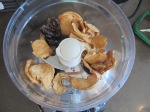 Add the dried apples, dates, and honey to the bowl of a food processor.