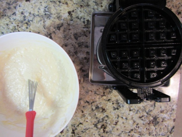 Prep a waffle iron by spraying with cooking spray and heating up.  Pour enough dough in the waffle iron to cover the grates.