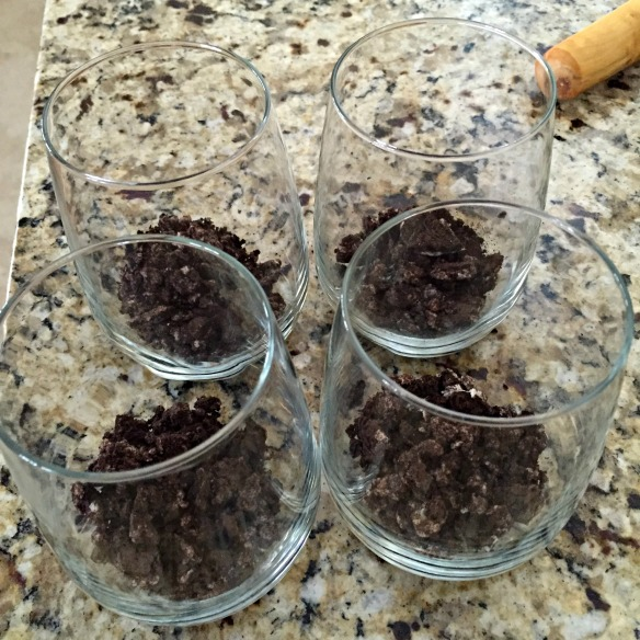 Spoon crushed Oreos into glasses.