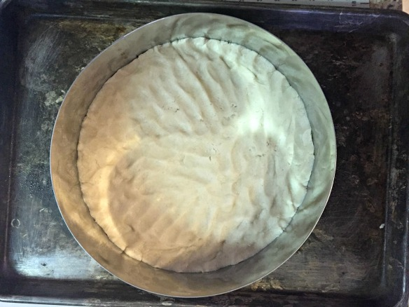 Press dough out in pizza pan. I didn't have a pizza pan so I used a large cake cutter to shape my dough...not the easiest route, but I don't have a pizza pan. I think a large round cake pan would work, too.