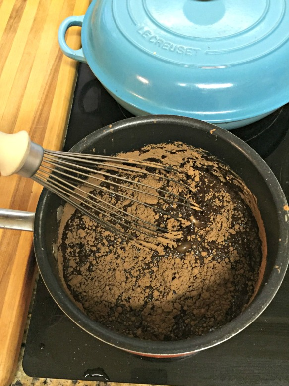 Now let's prepare the glorious filling. Combine 2 1/2 cups of water with the sugar, corn syrup, and cocoa powder in a large saucepan. Bring to a boil, whisking constantly.