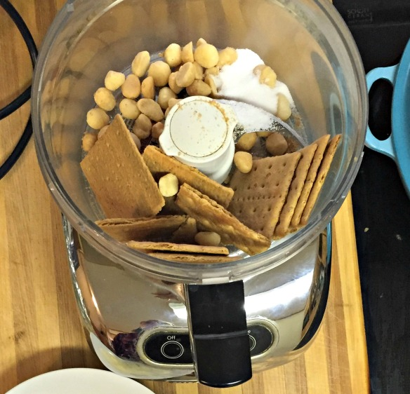 Place graham crackers, macadamia nuts, and sugar in the bowl of a food processor. Pulse until crumbs form.