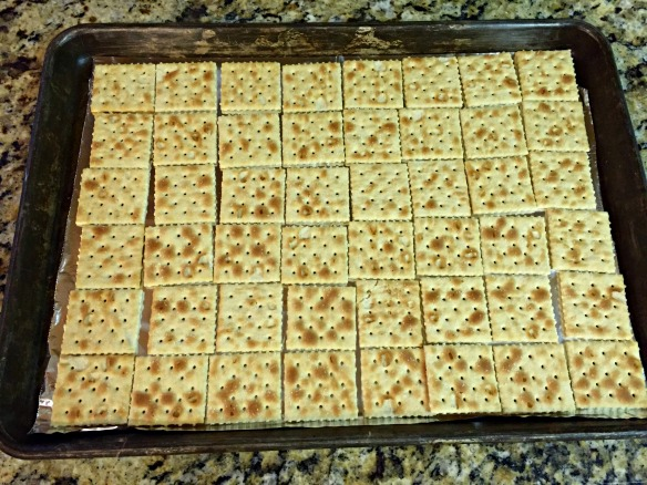 Lay out the saltines on a foil-lined baking sheet.